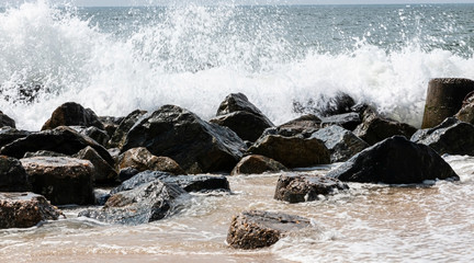 Ocean waves crashing on a jetty of rocks on the beach Wall mural