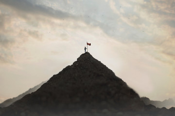 woman plants his flag on the mountain peak as a sign of success Wall mural