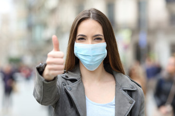 Happy woman with mask gesturing thumbs up
