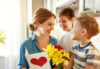 Papiers peints Narcisse Happy children giving card and flowers to mother.