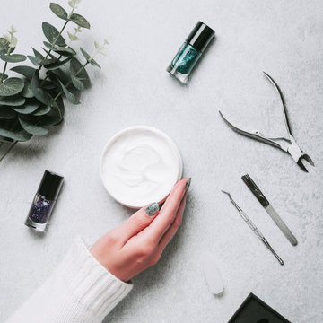 Woman hands, nail polish, manicure tools and hand cream on grey concrete table top flat lay. How to do manicure at home concept. Do manicure by yourself while staying at home, top view