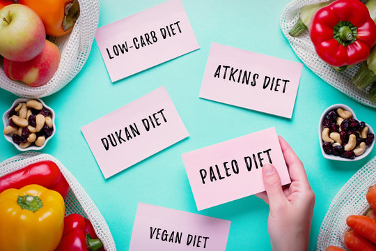 Woman choosing between popular diets for weight loss with fresh fruits, nuts and vegetables in background. Stickers with popular diet names on blue, healthy lifestyle concept, flat lay, top view