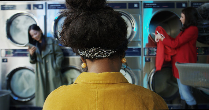 Rear of African American stylish woman in laundry service room. Mixed-races female clients of small washhouse. Back view on girl sitting and waiting while washing machines working and cleaning clothes