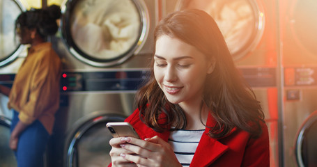 Caucasian young pretty and stylish girl in yellow glasses standing in laundry service room and tapping on smartphone. Woman texting message on phone while waiting for clothing to be washed.