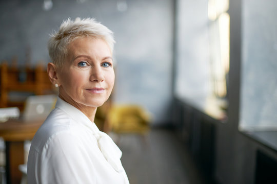Isolated image of beautiful stylish middle aged female entrepreneur with neat make up going to business meeting, standing against office interior background, looking at camera with confident smile