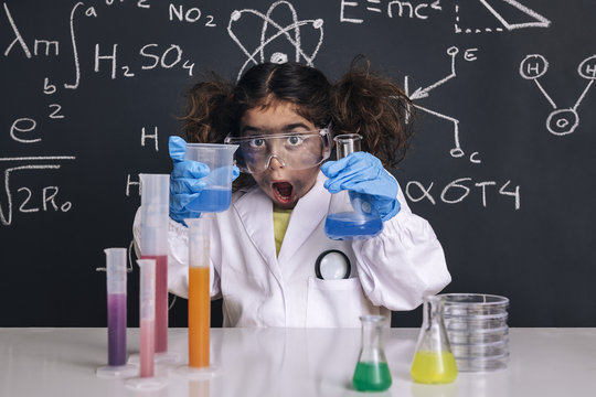 surprised scientist girl with gloves in lab coat