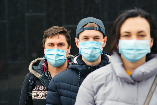 Coronavirus epidemic. People wearing face mask outdoors. Group of young volunteers. Coronavirus quarantine.