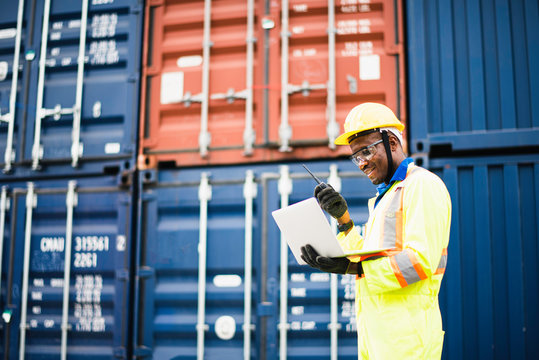 Adult African american men worker Check and control loading freight Containers by use computer laptop at commercial shipping dock smiling felling happy. Cargo freight ship for import export concept