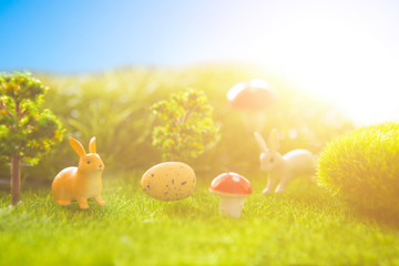 Easter eggs and rabbits. Holiday nature concept with easter hunt. Eggs in the sunny meadow.