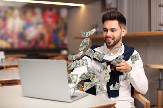 Man with modern laptop and flying dollar banknotes at table indoors. People make money online