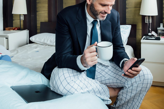 Businessman sitting on the bed with smart phone and coffee