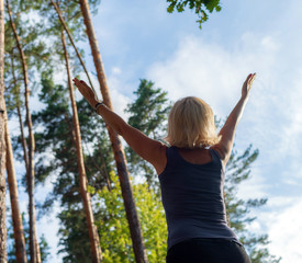 Blonde in the forest with arms raised to the sky. Selective focus.