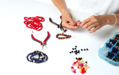 Jewelry making. Making a bracelet of colorful beads. Female hands with a tool on a white background.