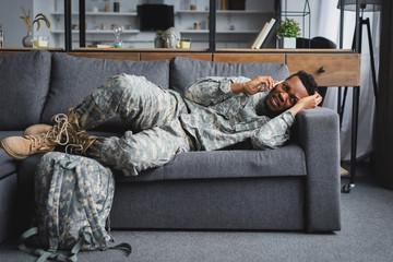 stressed african american soldier in military uniform talking on smartphone and suffering from PTSD at home with backpack