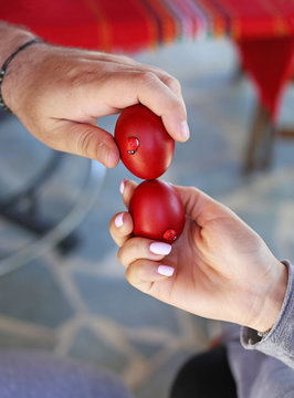 hands holding cracked red Easter eggs - Orthodox greek tradition of cracking eggs - symbolizes Christ resurrection