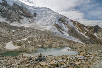 Wall Mural - Small lake on Hohsaas with beautifull views on Trift glacier in Swiss Alps
