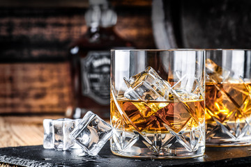 Glass of whiskey with ice cubes on black stone table. Side view with copy space alcohol concept. Fototapete