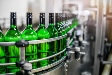 Bottling and conveyor line or belt at winery factory, Wine bottles filling production.
