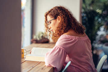 Young red hair woman with eyeglasses is sitting and reading a book  Fototapete