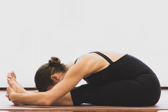 Flexible woman on seated forward bend pose with black overalls and hands holding feet. Female yogi on paschimottanasana over white background. Bright yoga studio, wellness, self care concepts