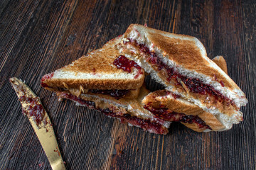 messy peanut butter and jelly sandwiches cut in half in stack