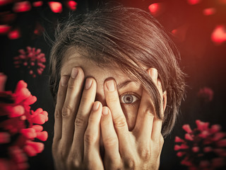 Wall Mural - Concept of fear of coronavirus. Woman covers her face her hands on background with coronavirus.