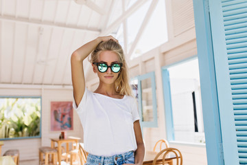 Confident blonde girl touching her hair while posing in sunglasses. Indoor photo of fashionable tanned young woman in white t-shirt.