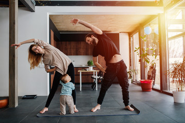 Mother and father doing morning exercises while spending time with their child Wall mural