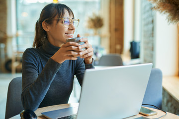 Attractive smiling woman enjoying coffee while working in cafe or coworking space. sitting at the desk with laptop looking at window. Concept remote work, freelance, using laptop computer or net-book.