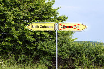 Yellow road signs pointing in opposite directions with German text Bleib Zuhause meaning Stay Home,  and Coronavirus, rural landscape in the background, pandemic health care concept, copy space