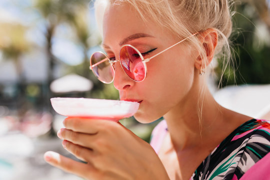 Close-up portrait of tanned woman drinking cocktail with eyes closed. Photo of chilling blonde girl in pink sunglasses tasting cold beverage.