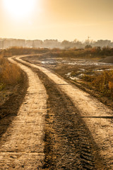 Fototapete - dirt road near a city with orange sky in the background