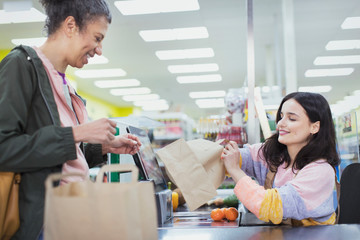 Female cashier helping customer bag groceries at supermarket checkout