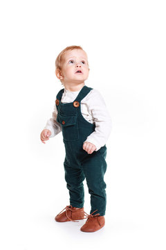 A one-year-old boy in a green jumpsuit