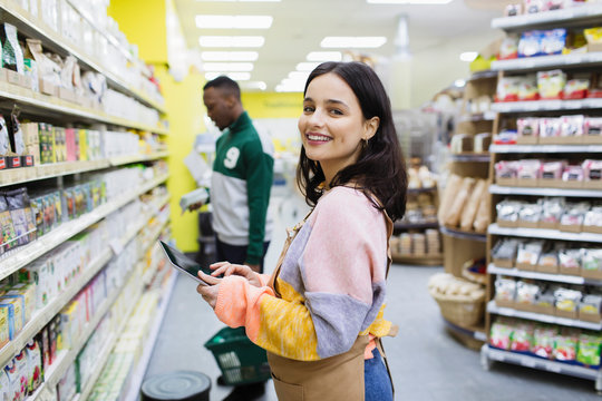 Portrait smiling female grocer with digital tablet in supermarket