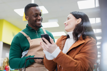 Grocer helping customer with smart phone in supermarket
