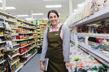 Portrait smiling confident female grocer working in supermarket Wall mural