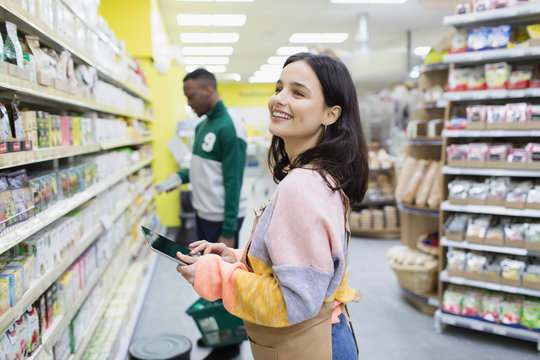 Smiling female grocer with digital tablet working in supermarket