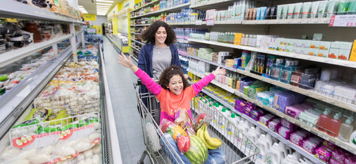 Mother pushing playful daughter in shopping cart in supermarket aisle