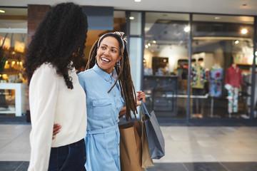 Smiling women friends shopping in mall