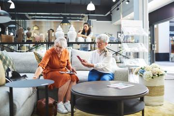 Senior women shopping for sofa in home decor shop
