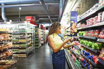 Woman with smart phone shopping in supermarket produce section