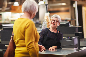 Happy senior female cashier greeting customer at supermarket checkout