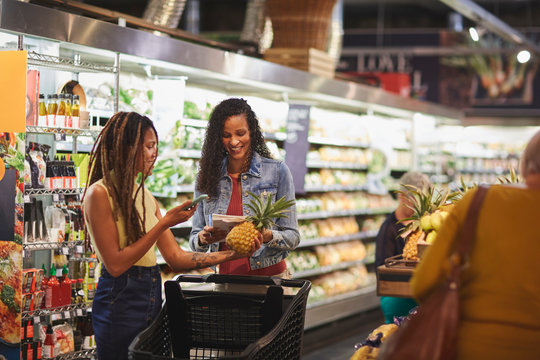 Women shopping for pineapple in supermarket produce section