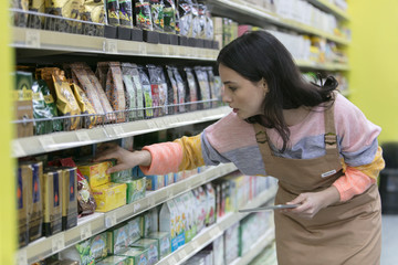 Female grocer with digital tablet checking inventory in supermarket