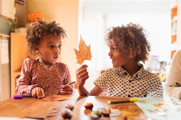 Brother and sister making autumn crafts at table