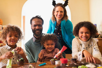 Portrait happy family decorating Halloween cupcakes at table