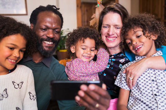Happy multiethnic family taking selfie with camera phone