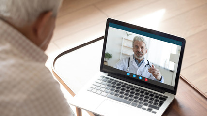 Poster Op straat Back view of mature man have video call consultation with male doctor using laptop Webcam, close up of elderly male patient talk speak with GP or physician at home, discuss illness, consult online