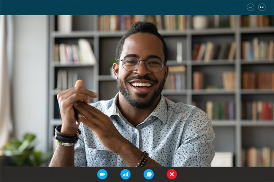 Headshot portrait screen application view of overjoyed young African American man sit at home have pleasant web conference on computer, smiling biracial millennial male talk on video call online